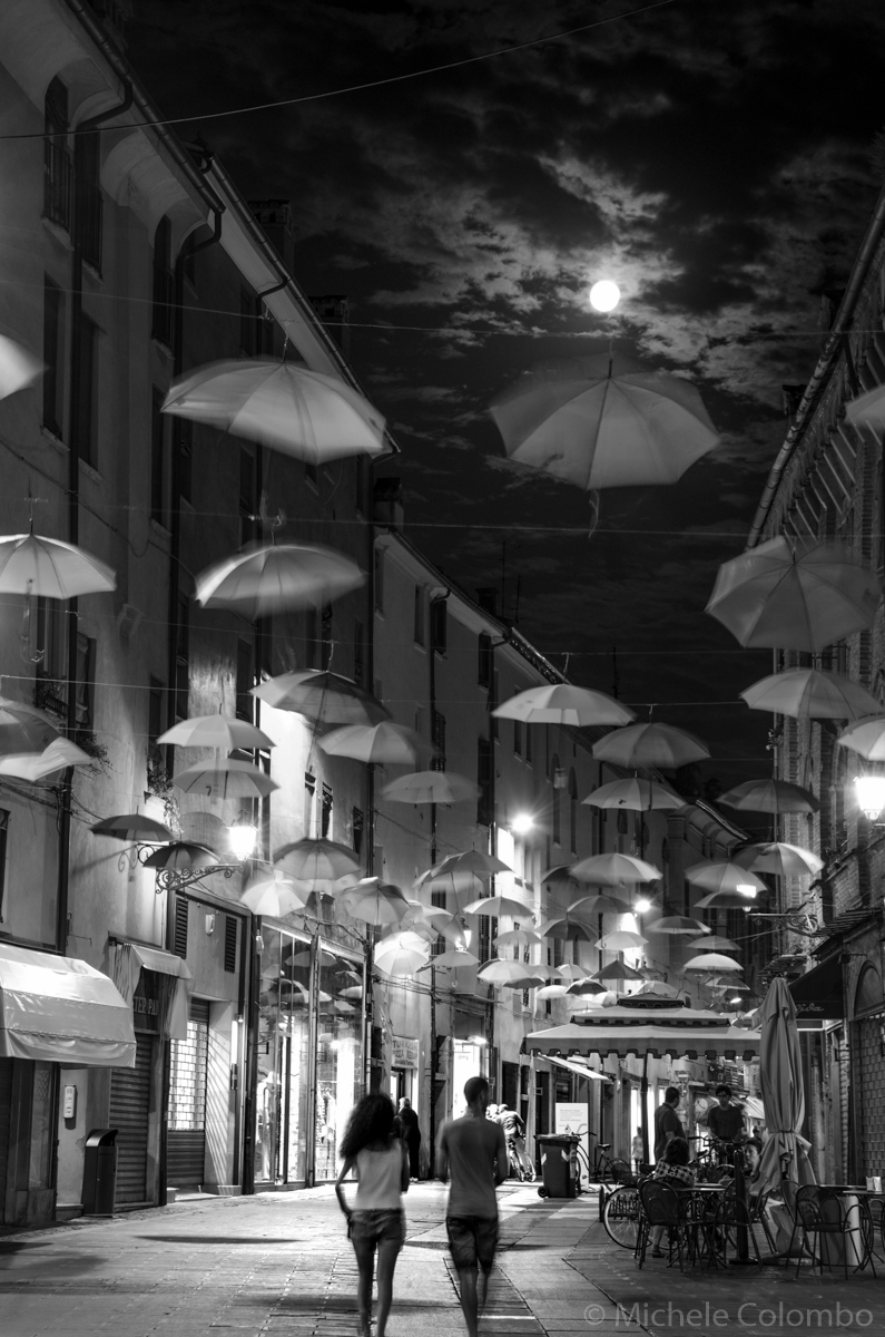 via Mazzini (Ferrara) with umbrellas and moon