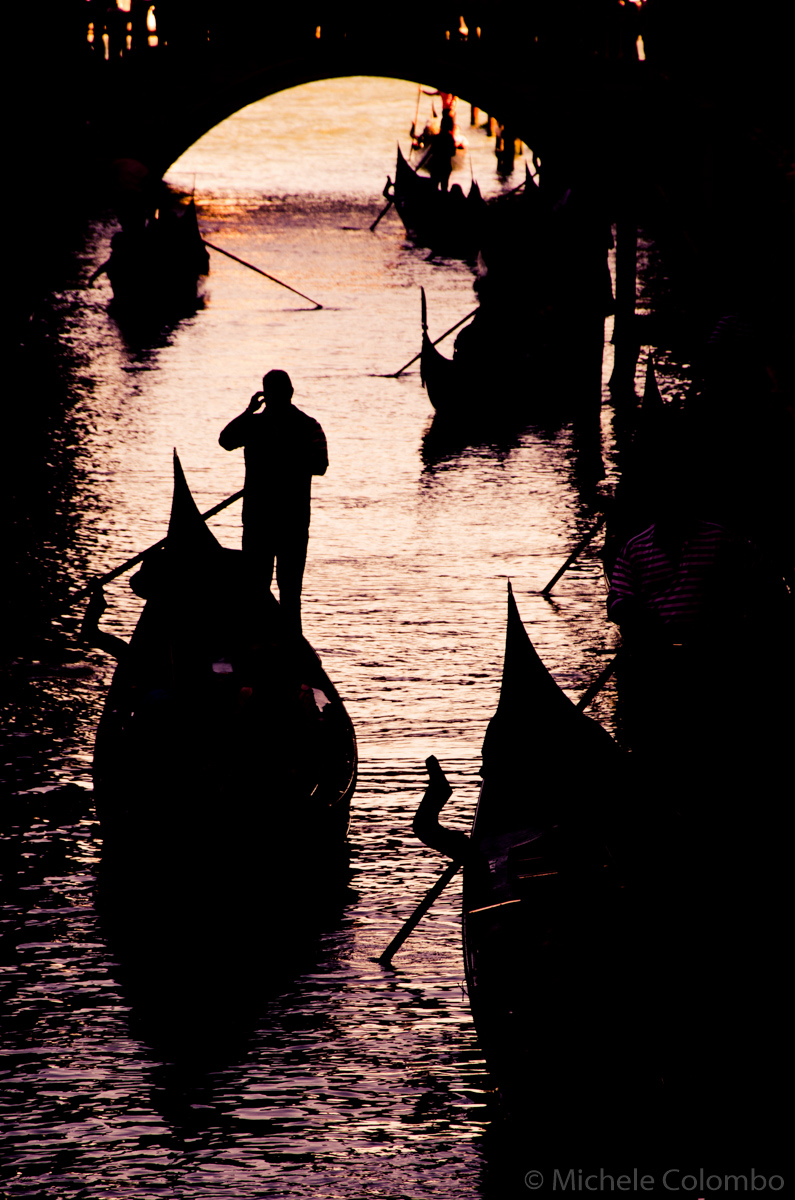 Silhouette of gondoliers at sunset