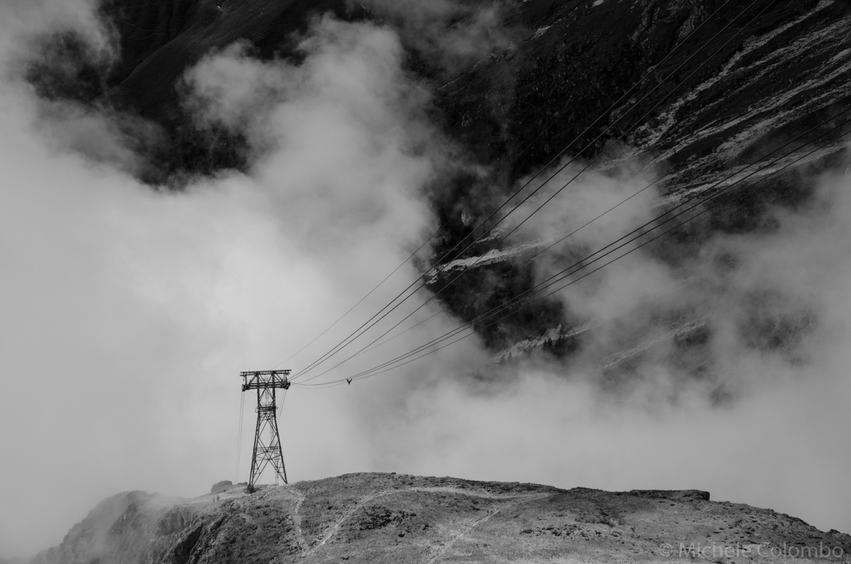 Dramatic black and white shot of a cable car pylon