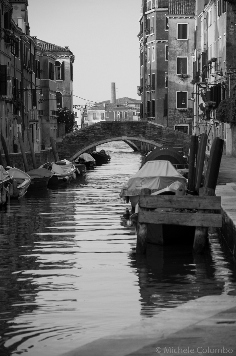 Black and white photo of boats in a canal in Venice