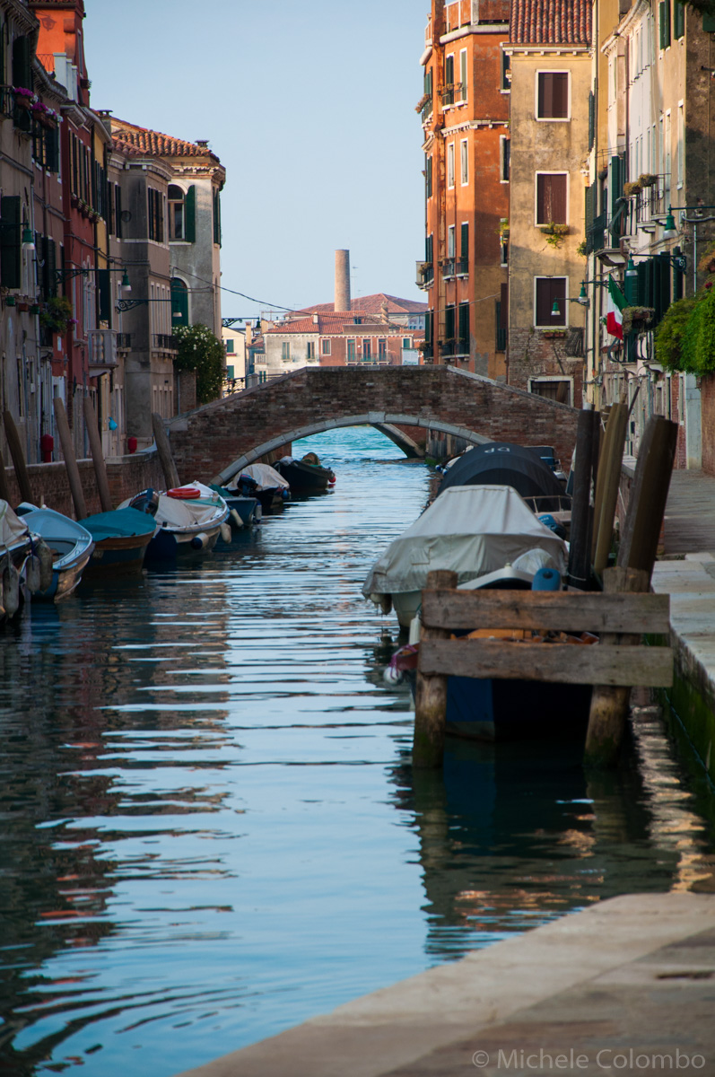 boats docked along a venice canal in the morning