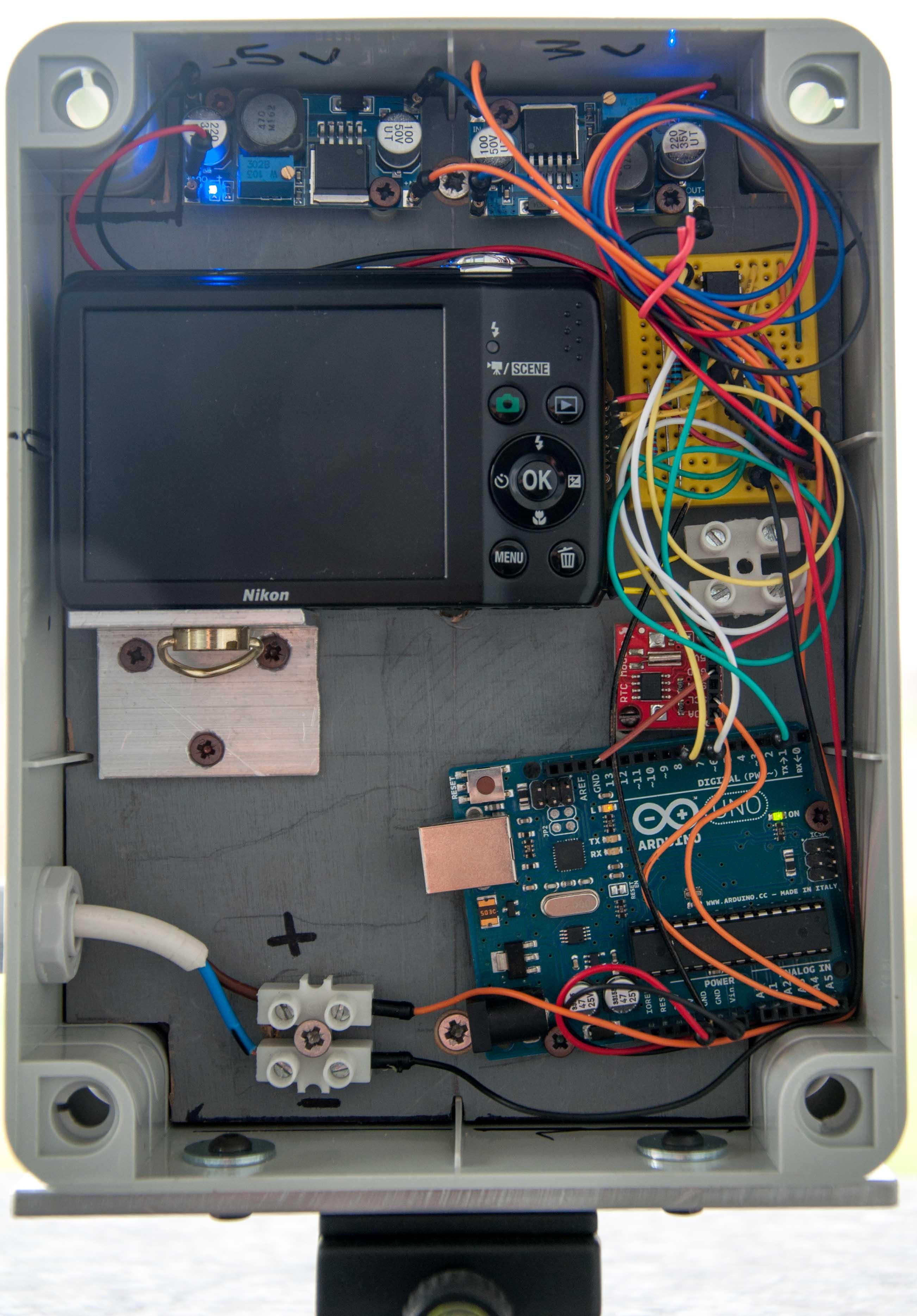 Arduino, il modulo RTC, la fotocamera,, la breadboard e i due regolatori di tensione collegati e inseriti nel case.